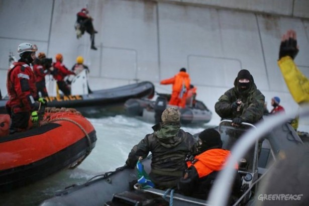 A Russian coast guard officer points a gun at a Greenpeace activist. The Arctic 30, seized while protesting drilling in the Arctic, are being detained on piracy charges. (Denis Sinyakov/Greenpeace)
