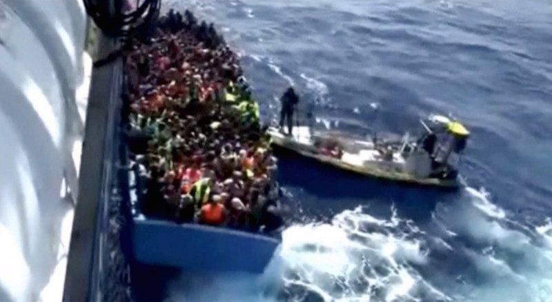 A boat full of migrants is seen next to Swedish ship Poseidon during a rescue operation in the sea off the coast of Libya in this still image taken from an August 26, 2015 video. REUTERS/Swedish Coast Guard Handout