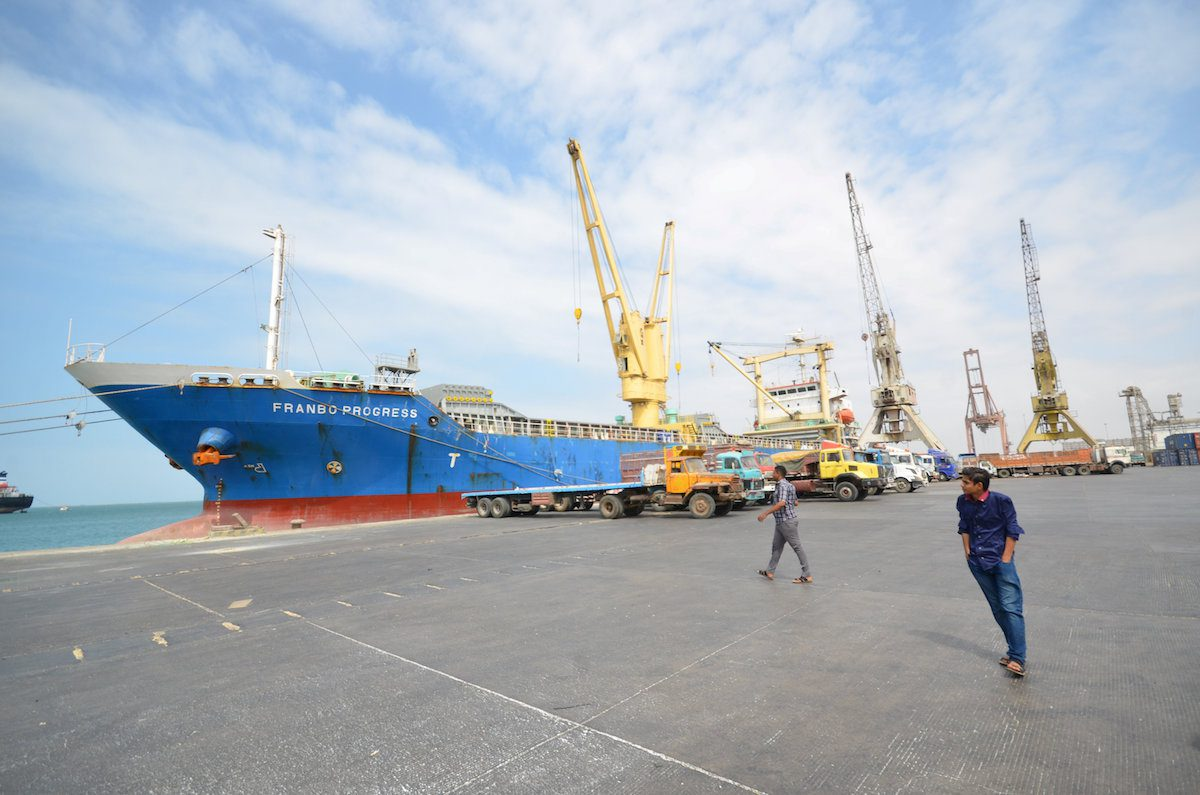 FILE PHOTO - People walk past a ship docked at the Red Sea port of Hodeidah