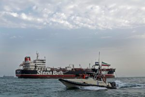 A boat of Iranian Revolutionary Guard sails next to Stena Impero, a British-flagged vessel owned by Stena Bulk, at Bandar Abbas port